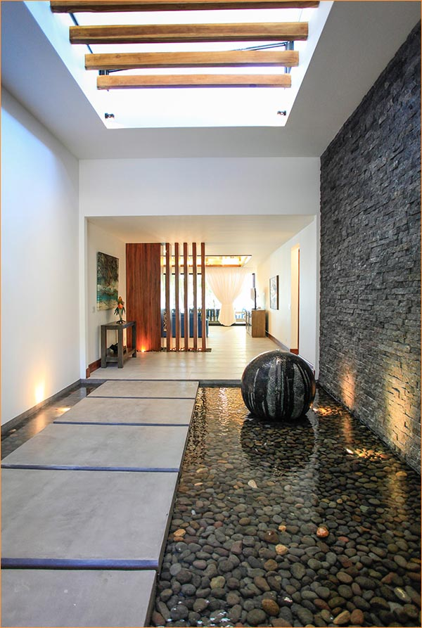 Restful stone and water art welcomes guests to this quiet beachfront villa.